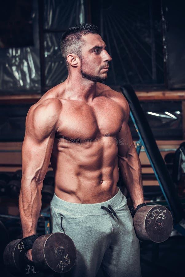 Halterofilista muscular que faz exercícios com pesos fotografia de stock