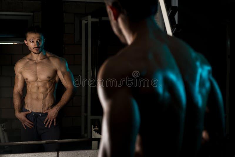 Halterofilista novo que dobra os músculos foto de stock royalty free