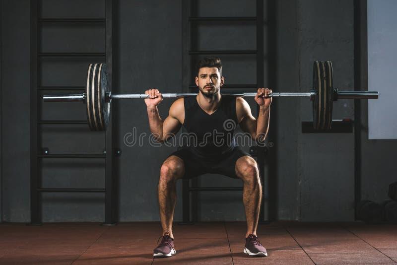 Halterofilista novo que faz o exercício com o barbell em ombros foto de stock royalty free