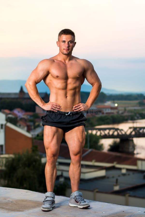 Halterofilista que dobra os músculos em um telhado foto de stock royalty free
