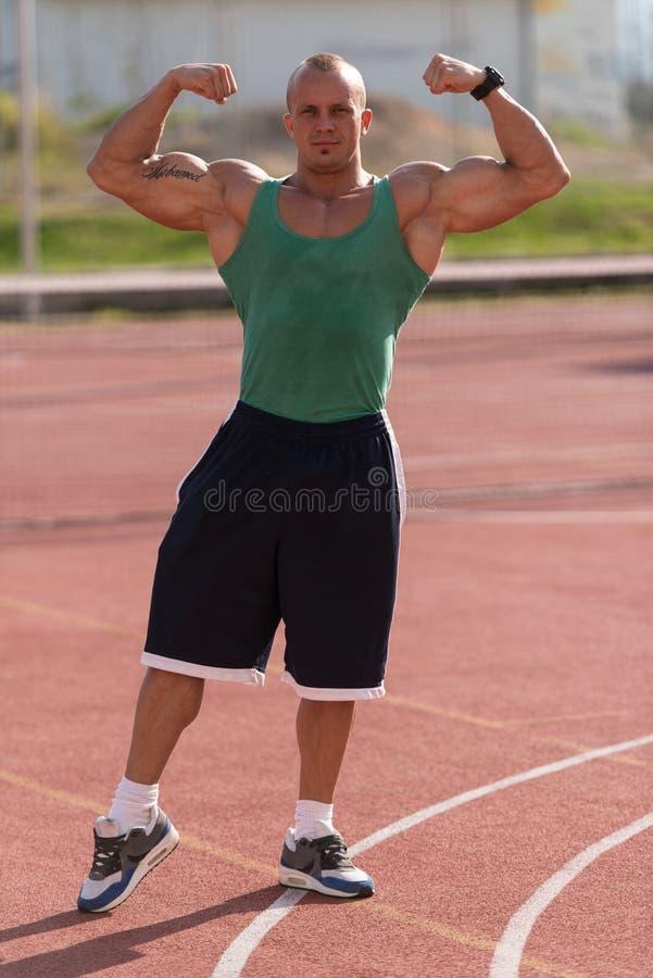Halterofilista que executa o lugar de Front Double Biceps At Tennis fotos de stock royalty free