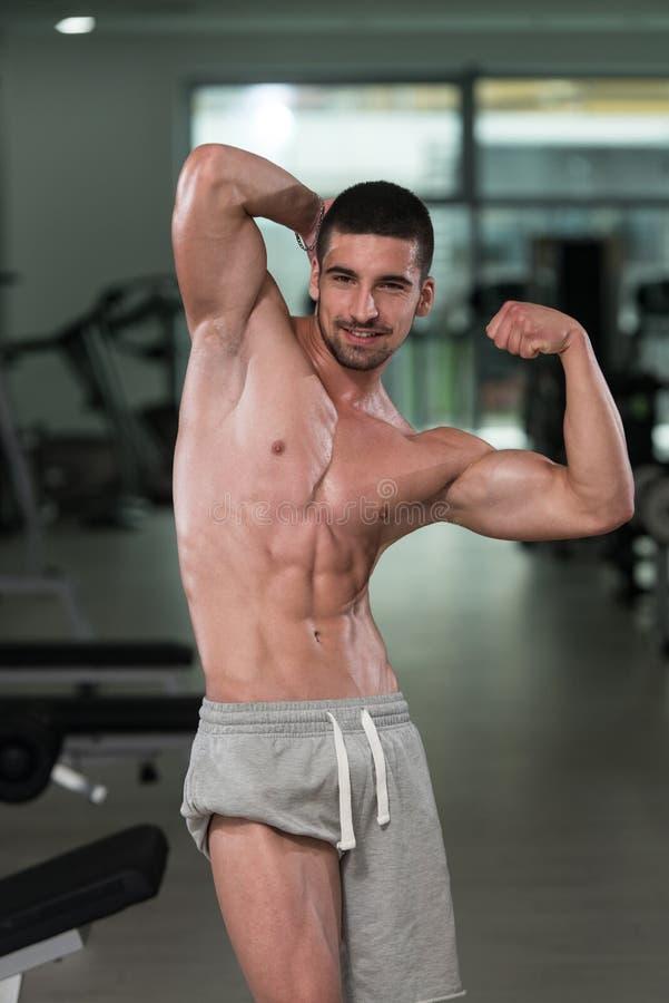 Halterofilista que executa a pose traseira do bíceps imagens de stock