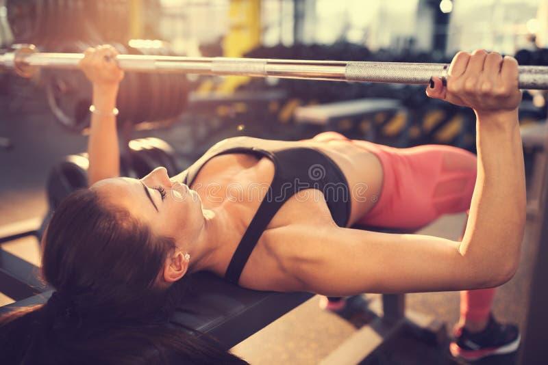 Halterofilista que exercita com o barbell no gym fotografia de stock royalty free