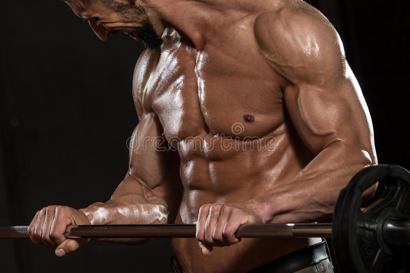 Halterofilista que exercita o bíceps com Barbell fotos de stock royalty free