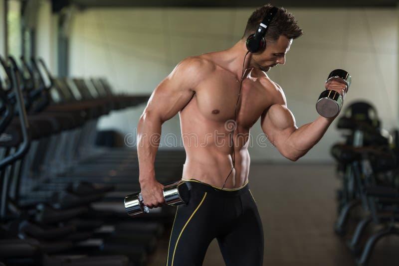 Halterofilista que exercita o bíceps com pesos fotografia de stock