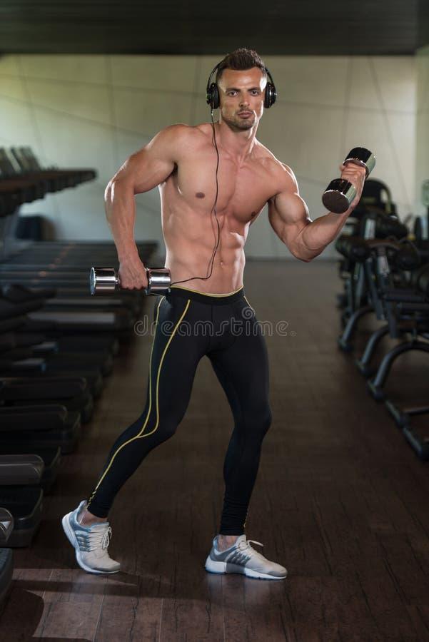 Halterofilista que exercita o bíceps com pesos imagem de stock
