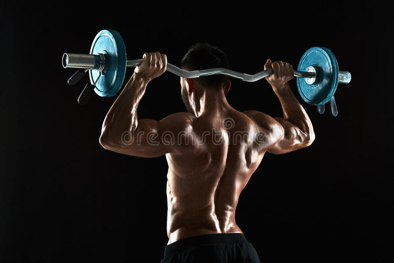 Halterofilista que levanta um barbell no fundo preto fotografia de stock