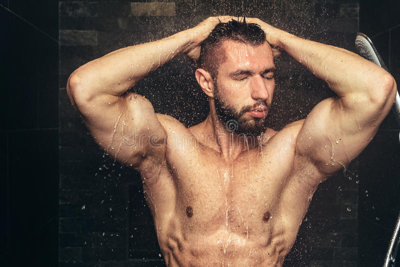 Halterofilista que toma o chuveiro após a formação O homem considerável no chuveiro com água deixa cair e espirra fotografia de stock royalty free