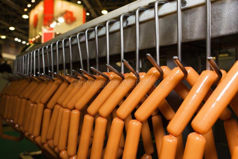 Halterung mit Wurst auf der Beförderung des Maschinenverkehrsgürtels lizenzfreie stockfotografie