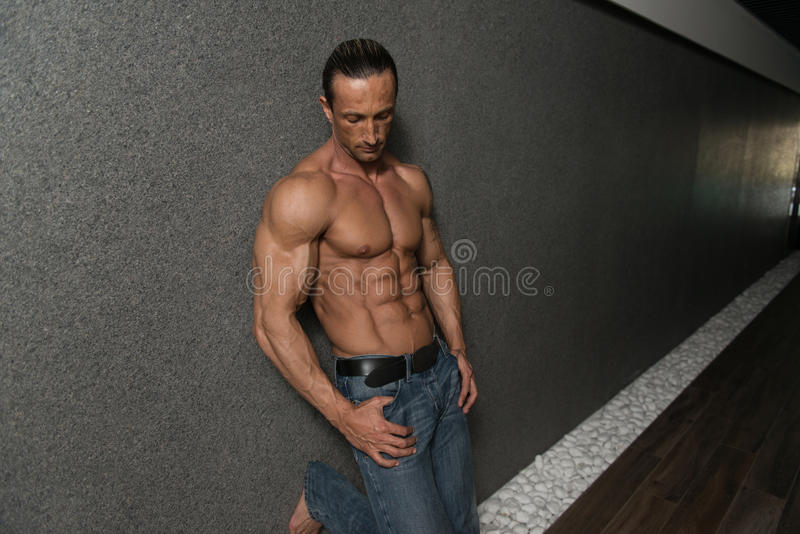 Haltungen des gutaussehenden Mannes im modernen Korridor lizenzfreie stockfotos