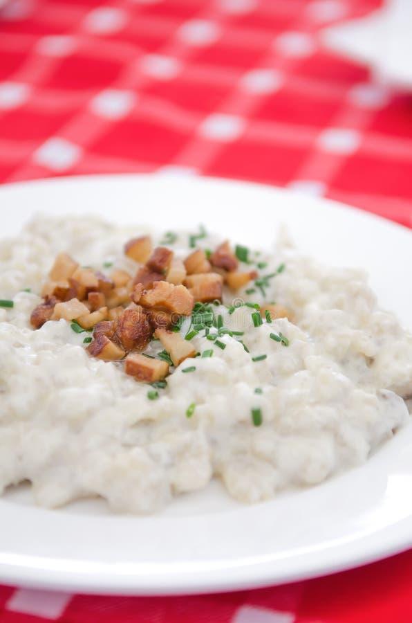Halusky con el queso y el tocino, que de las ovejas de Bryndza es bola de masa hervida de la pasta de la patata, gnocchi similar  imagen de archivo libre de regalías