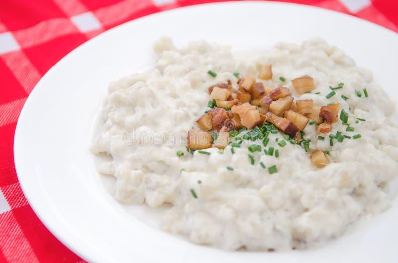 Halusky con el queso y el tocino, que de las ovejas de Bryndza es bola de masa hervida de la pasta de la patata, gnocchi similar  imagen de archivo