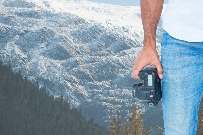 Halv del av en man som rymmer en kamera främst av snö-täckte berg fotografering för bildbyråer