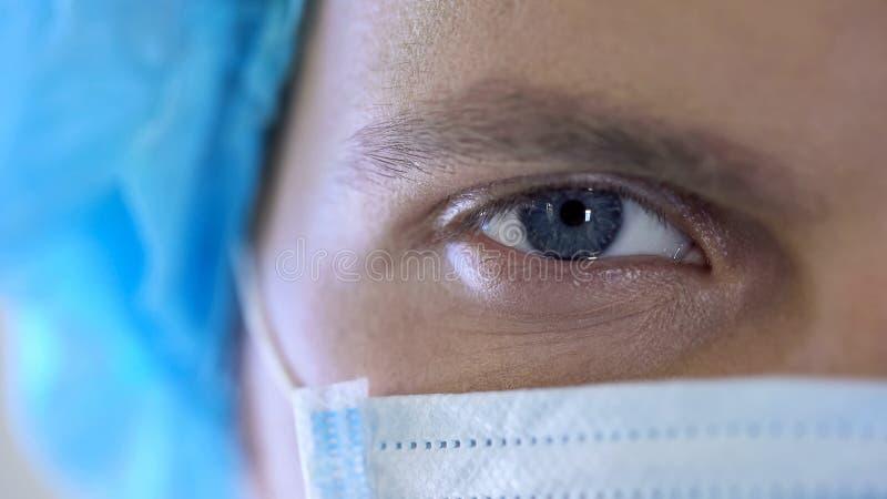 Halv framsida för doktorer i maskeringen, manlig terapeut som poserar för kameran, förtroende i klinik royaltyfria bilder