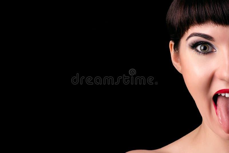 Halv framsida för emotionell kvinna med tungan ut fotografering för bildbyråer