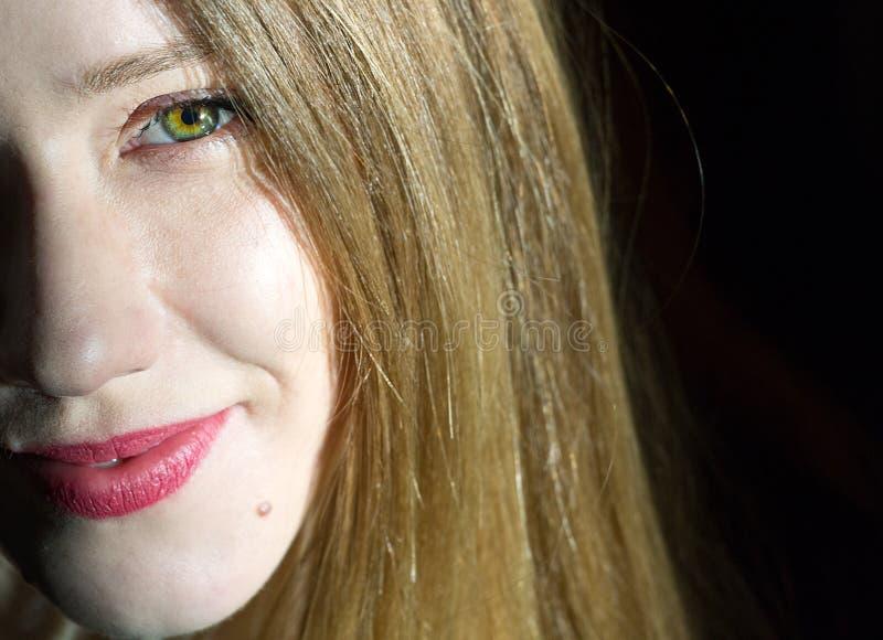 Halv framsidaheadshot av en blond ung kvinna, svart bakgrund royaltyfria foton