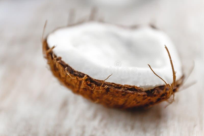 Halv kokosnöt på en ljus vit träbakgrund, closeup Top beskådar royaltyfria foton