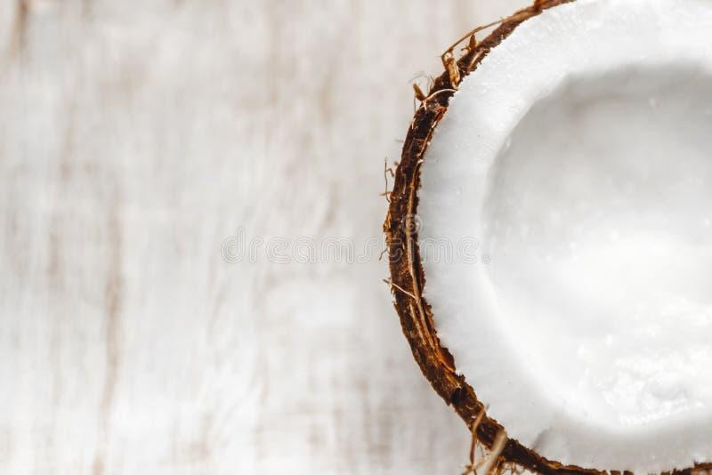 Halv kokosnöt på en ljus vit träbakgrund, closeup Top beskådar royaltyfria bilder