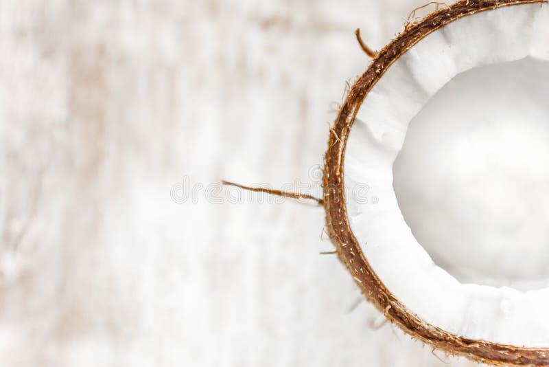 Halv kokosnöt på en ljus vit träbakgrund, closeup Top beskådar arkivfoton