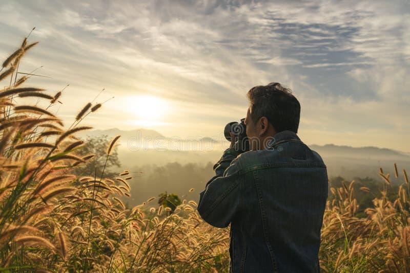 Halv längdbaksida av en Caucasian man som tar fotoet av det dimmiga berget i soluppgångtid arkivbild