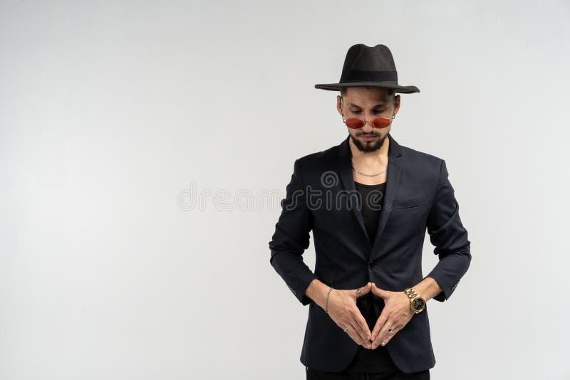 Halv längdstående av den unga stiliga allvarliga moderna mannen som bär den svarta dräkten och hatten i rund solglasögon royaltyfria bilder