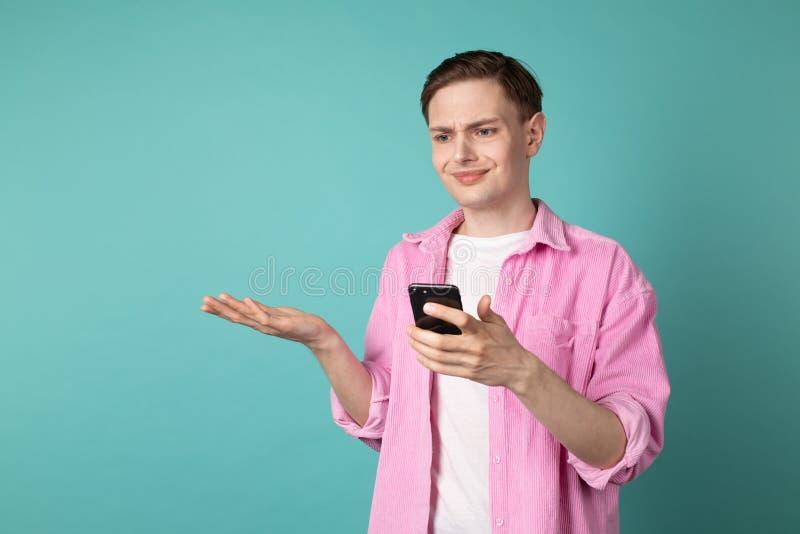 Halv längdstående av en förvirrad olycklig man i rosa skjorta arkivfoto