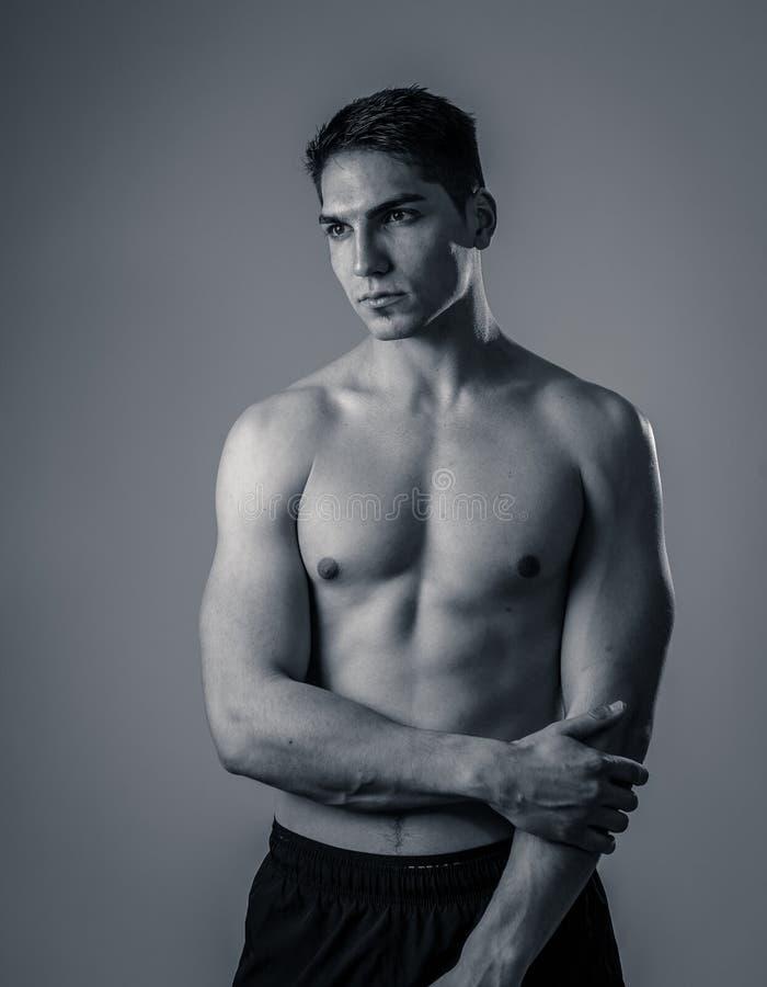 Halv l?ngdst?ende av den starka sunda stiliga idrotts- mannen som isoleras p? neutral bakgrund arkivbild
