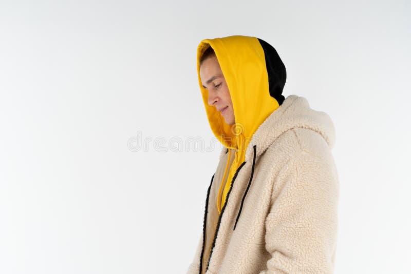 Halv l?ngdst?ende av den unga upprivna olyckliga mannen som b?r gult hoodieanseende mot vit bakgrund, copyspace f?r royaltyfria foton