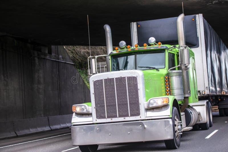 Halv lastbil för klassisk stor rigggräsplan som transporterar kommersiell last i den dolda svarta halva släpet som kör under bron royaltyfria foton
