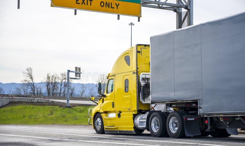 Halv lastbil för ljus gul stor rigg som transporterar gods i den halva släpet som täckas med svart gummerat tyg som kör på d arkivfoton
