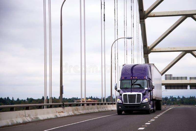 Halv lastbil för purpurfärgad stor rigg med torra skåpbil släp för länge - transportsträckabil fotografering för bildbyråer