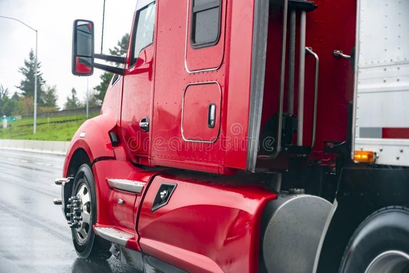 Halv lastbil för röd stor rigg med den halva släpet som kör på den våta vägen i regnväder royaltyfri foto