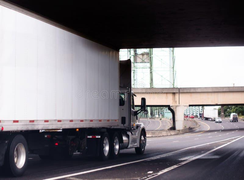 Halv lastbil för vit stor rigg med dagtaxin och torr skåpbil släp runnin arkivfoton