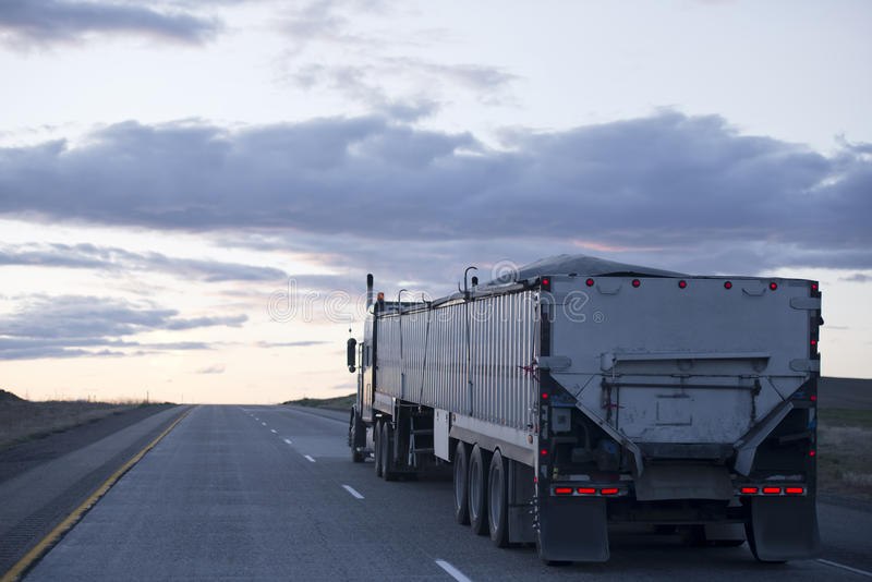 Halv lastbil med den långa släpet i stora partier på aftonvägen royaltyfri fotografi