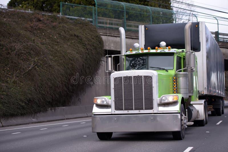 Halv lastbilflotta för grön amerikansk stor rigg som transporterar gods i Co royaltyfria bilder