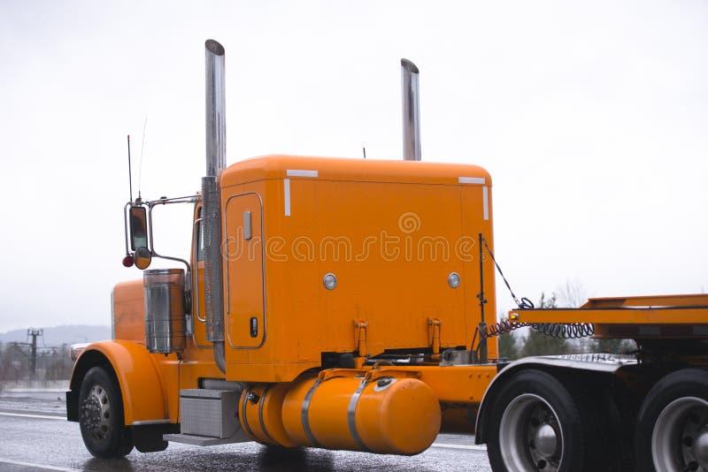 Halv lastbiltraktor för klassisk ljus orange stor rigg som transporterar fl royaltyfri foto