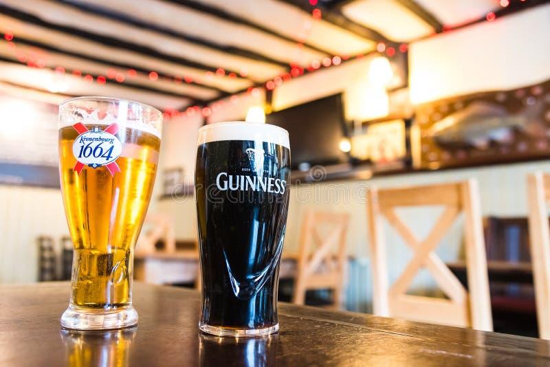 Halv liter av Guinness och Kronenbourg 1664 arkivfoton