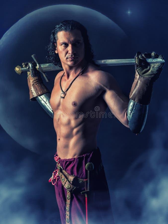 Halv naken krigare med ett svärd i mystikerbakgrunden royaltyfri foto