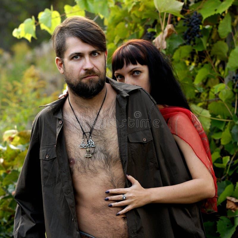Halv naken man och kvinna i lösa druvor royaltyfria bilder