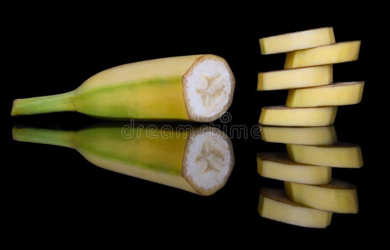 Halv söt gul banan och en pyramid av skivor med ljus reflexion i exponeringsglaset arkivbilder