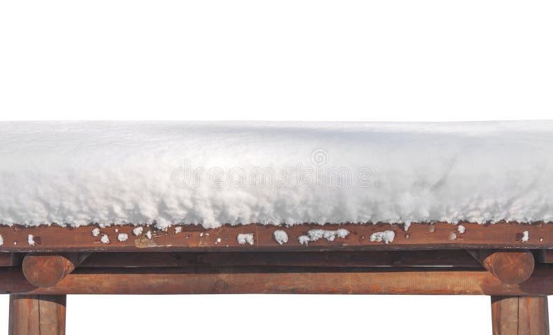 Halv sikt av trätabellen som täckas med snö och isoleras på vit fotografering för bildbyråer