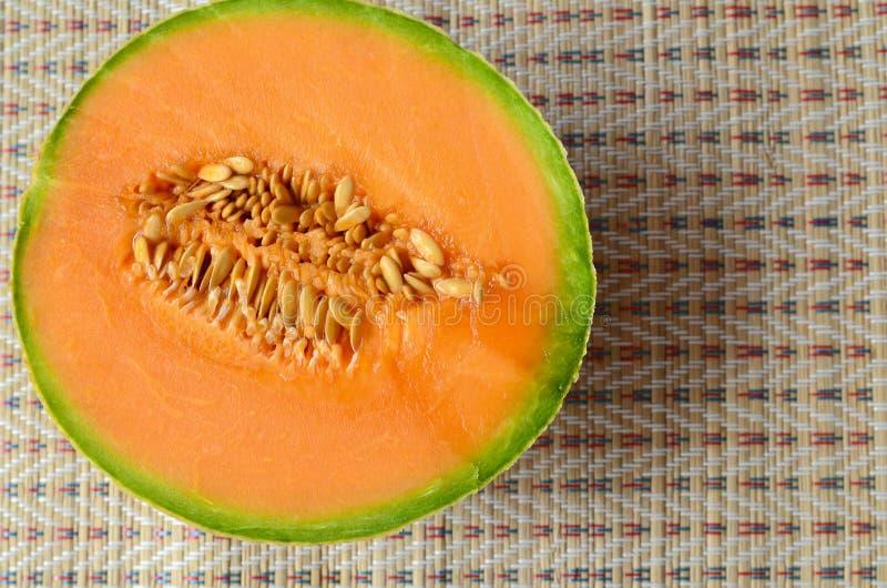 Halva av den mogna organiska cantaloupmelonmelonmuskmelonen, mushmelon, rockmelon på sugrörservett arkivbilder