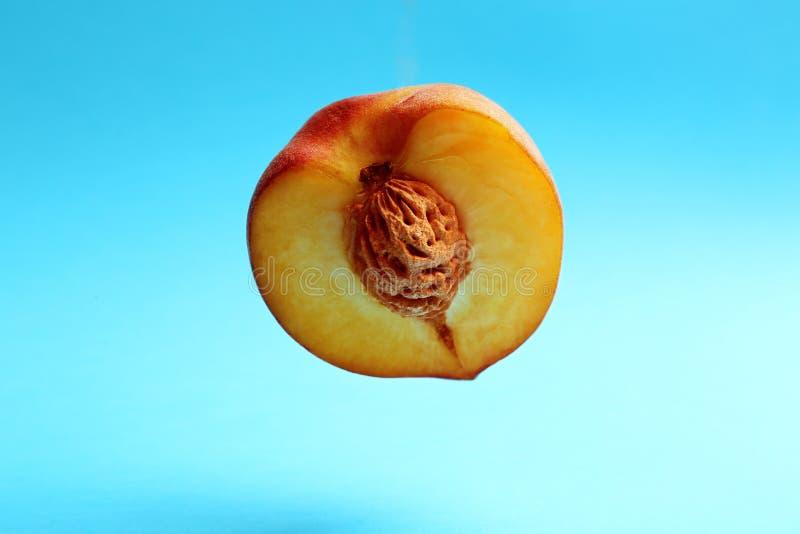 Halva av den nya saftiga persikan på blått arkivfoton