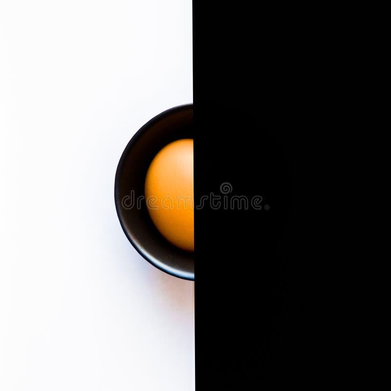 Halva av det orange ägget inom den svarta bunken på den vita bakgrunden på den vänstra och svarta bakgrunden på rätten Top beskåd fotografering för bildbyråer