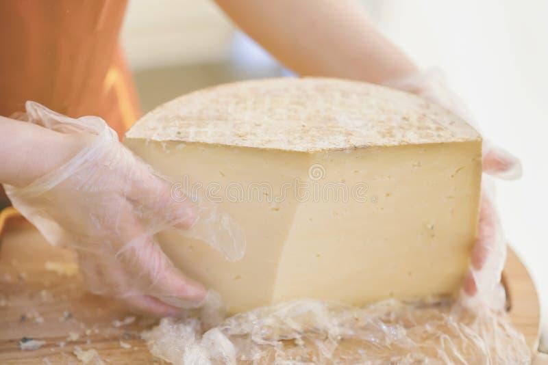 Halva av ett stort huvud av ost i händerna av säljaren i handskar, träbräde Selektivt fokusera Gastronomiskt mejeri arkivfoto