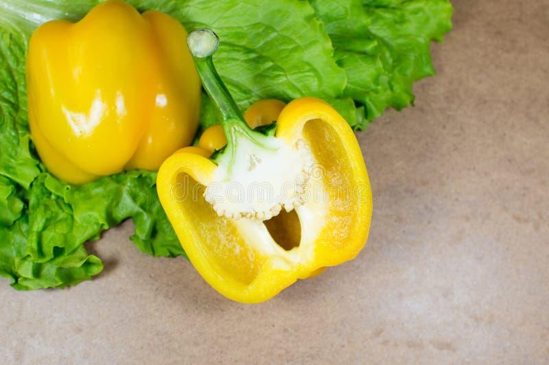Halva av gul peppar med grön sallad arkivfoton