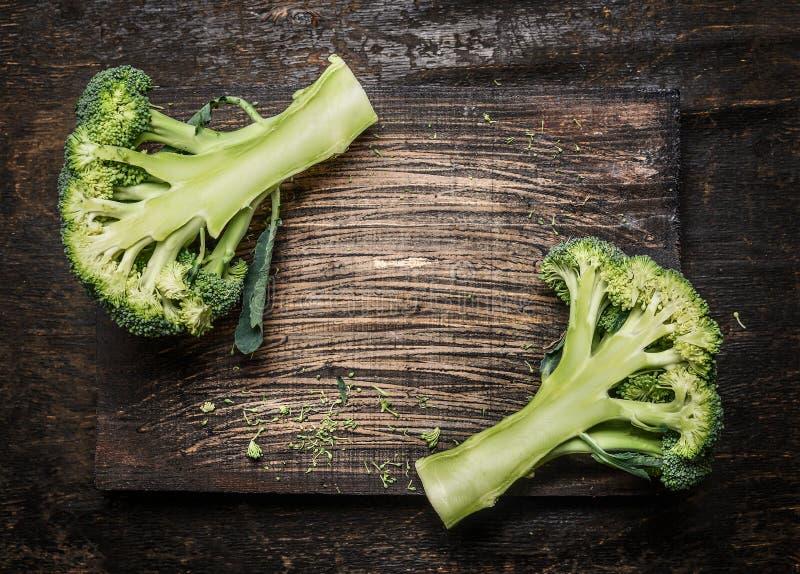 Halva av ny organisk broccoli på mörk lantlig träbakgrund, ställe för text royaltyfria bilder