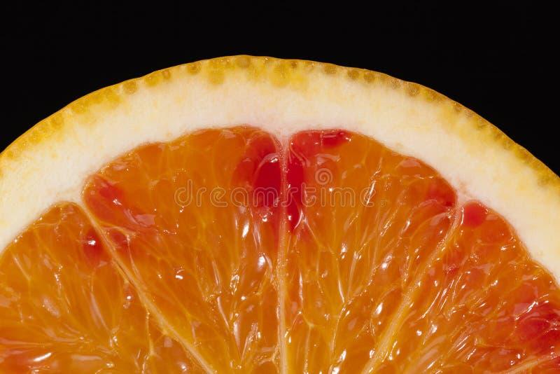 Halva av orange frukt som isoleras på svart bakgrund arkivbilder