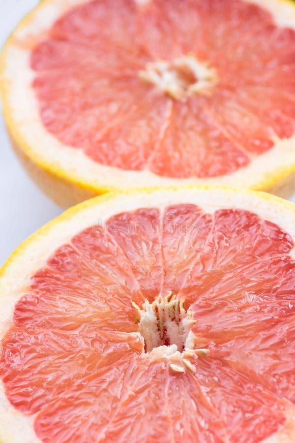 Halva cirkelskivor av den mogna saftiga röda halverade grapefrukten på vit bakgrund Sunda vitaminer bantar sommarDetoxstrikt vege arkivfoto