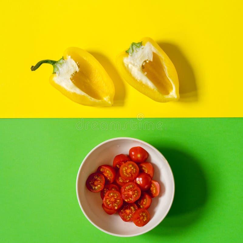 Halva en gul peppar på en gul bakgrund och en platta med en röd körsbärsröd tomat på en grön bakgrund arkivbild
